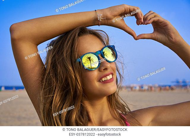 Brunette girl on beach sunglasses with palm tree reflection and fingers heart shape gesture