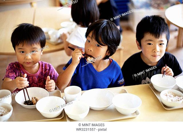 High angle view of three boys sitting at a table in a Japanese preschool, eating with chopsticks
