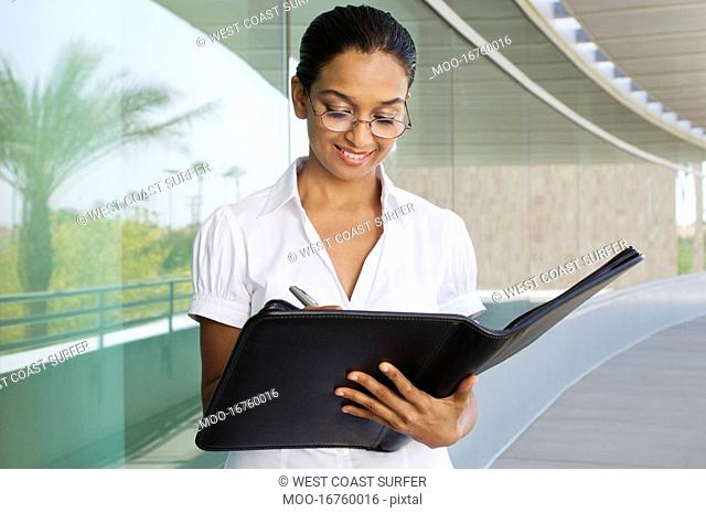 Young Woman Writing in a Planner