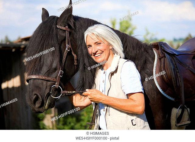 Germany, Bavaria, Mature woman hugging horse