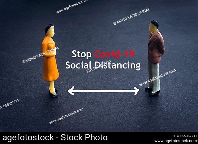 STOP COVID-19 SOCIAL DISTANCING text with miniature people on dark background. Covid-19 or Coronavirus concept