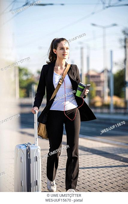 Young woman with luggage in the city on the move
