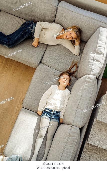 Happy mature woman and girl at home lying on couch