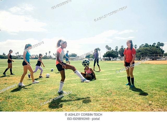 Schoolgirls practicing keepy uppy with soccer ball on school sports field