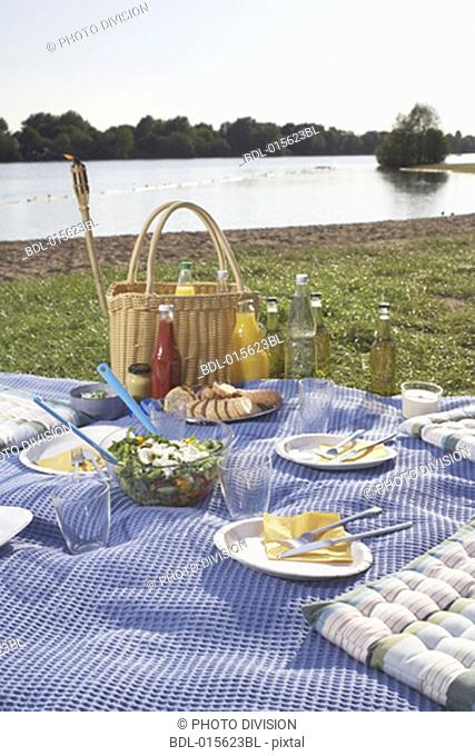 still life of place settings for picnic near lake