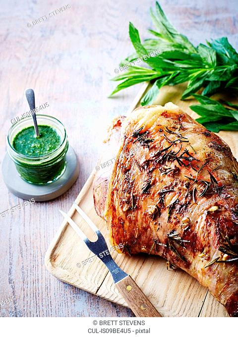 Roast leg of lamb on chopping board with jar of mint sauce, close-up