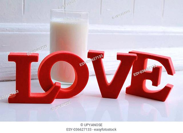 the words love in front of a glass of milk