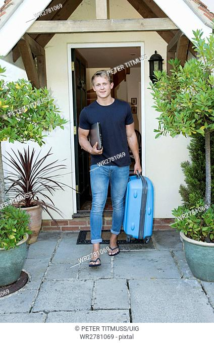 Teenager leaving home, A young man carrying a laptop and suitcase leaving home