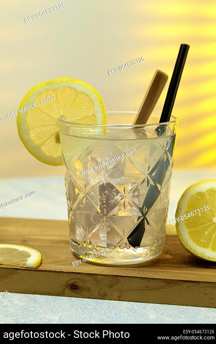 close-up of refreshing lemonade glass with ice, spoon and straw on cutting board on background with sunlight entering through rear window. Copy space