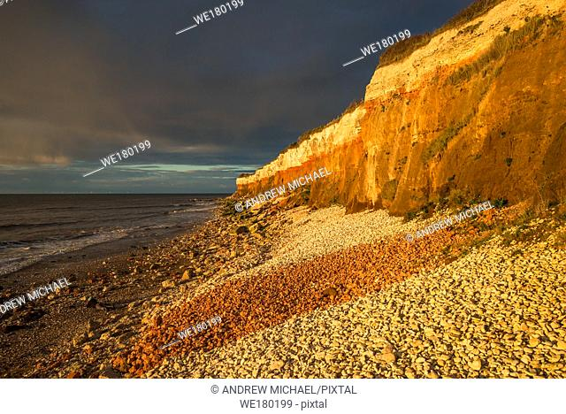 Hunstanton Cliffs at sunset with dark stormy sky, on Norfolk coast, where white chalk overlays red limestone in a colourful formation. England, UK