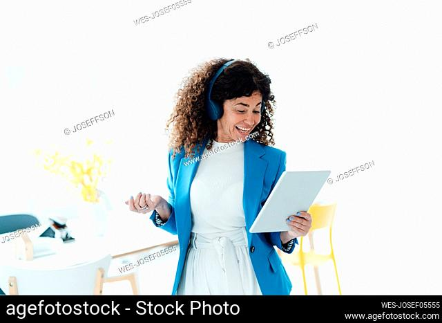 Smiling businesswoman with headphones using digital tablet in office