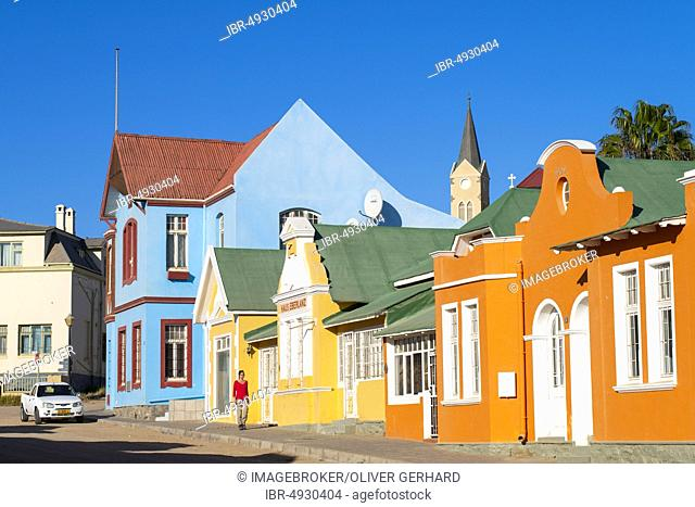 Colourful houses from German colonial times, behind the tower of the rock church, old town of Lüderitz, Namibia, Africa