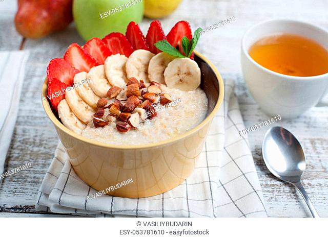 Bowl of oatmeal with a banana, strawberries, almonds, hazelnuts and butter on a rustic table. Hot and a healthy dish for Breakfast, top view