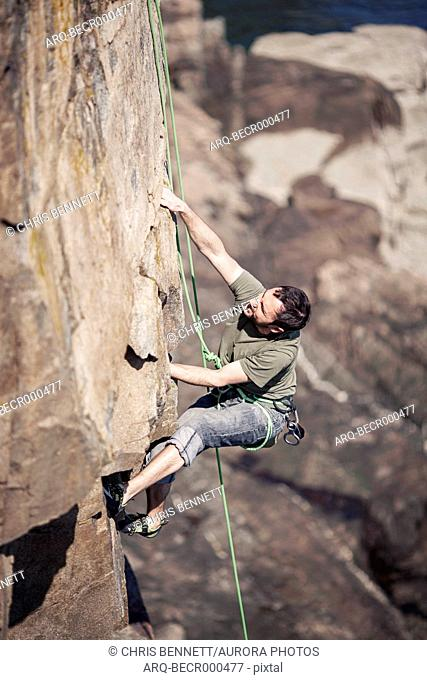 Adventurous young rock climber climbing at Otter Cliffs, Acadia National Park, Maine, USA
