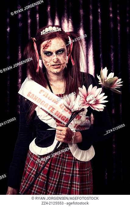 Violet the evil zombie prom queen with wicked rotten facial expression holding flowers on stage during an acceptance speech at the underground formal dinner...