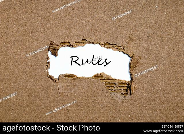 The word rules appearing behind torn paper