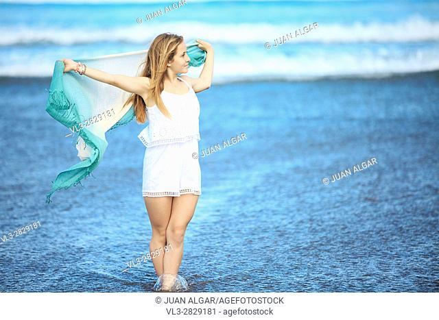 A lady with pareo walking on a coast. Horizontal outdoors shot