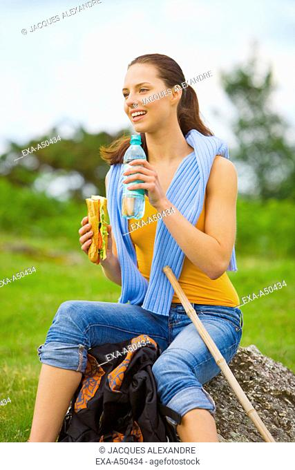 Young woman hiking making a rest, eating a sandwich and drinking water