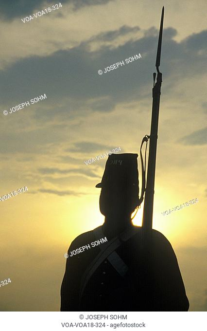 Silhouette of soldier at sunset with gun during reenactment of Battle of Manassas marking the beginning of the Civil War