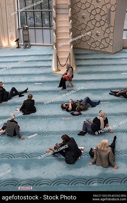 03 October 2021, North Rhine-Westphalia, Cologne: Interested visitors sit in the Ditib central mosque on Open Mosque Day