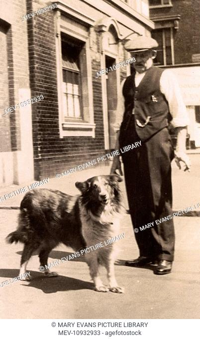 Man in his shirtsleeves with a collie dog in a street