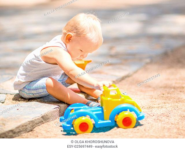 Little boy is playing toy car