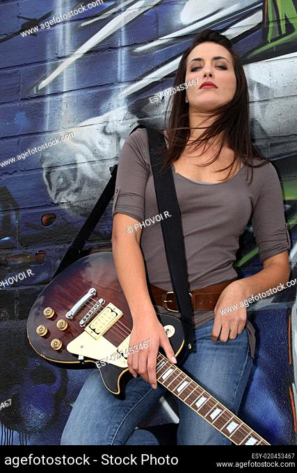 Cool female guitarist standing against graffiti