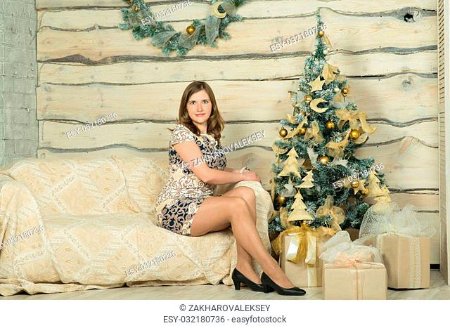 Young beautiful woman in blue evening dress sitting near Christmas tree and gifts for the New year. Interior Christmas decorations