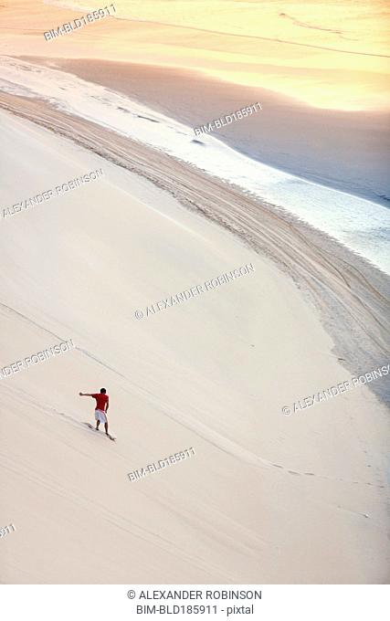 Man surfing on sand dunes on beach