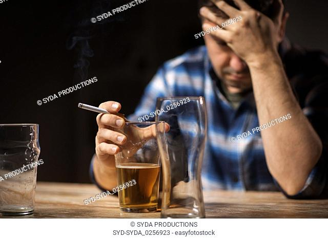 drunk man drinking alcohol and smoking cigarette