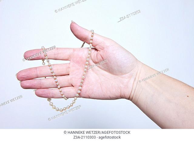 Hand Holding Antique Necklace, Hand Gesture, Studio shot