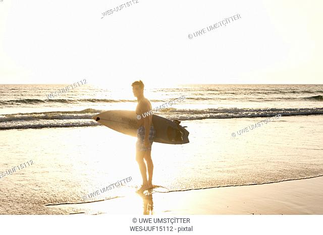 Young man walking on the beach, carrying his surfboard