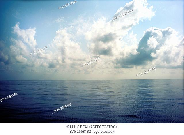 Calm Mediterranean sea with clouds in the blue sky