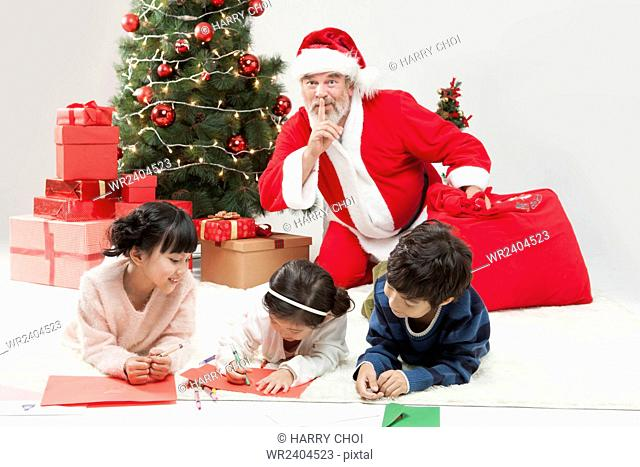 Three smiling children drawing and smiling Santa putting his finger on his lips behind them