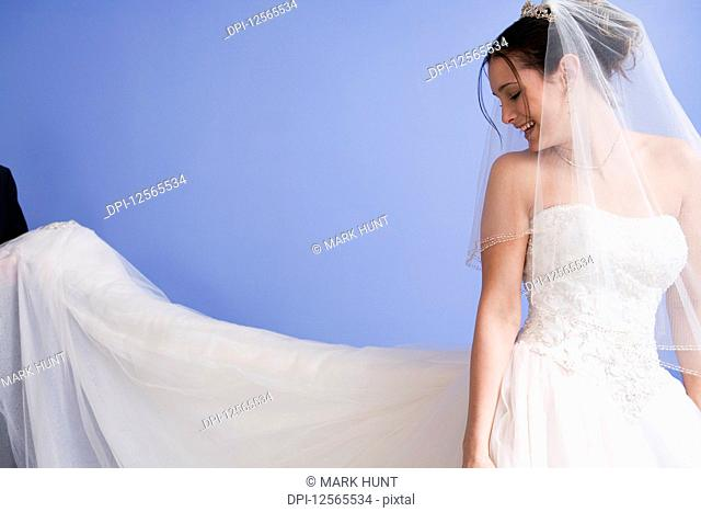 View of a smiling young bride in bridal gown