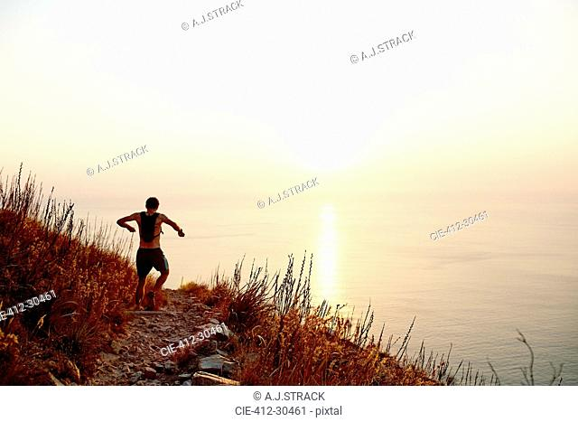 Male runner with backpack descending craggy trail overlooking sunset ocean