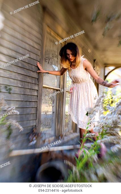 30 year old brunette woman wearing a dress balancing on some old wood on the porch of an old country house