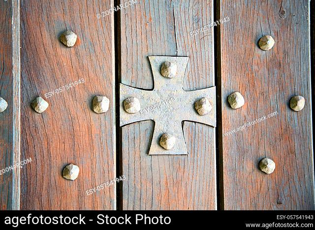 lombardy  arsago seprio abstract  rusty brass brown knocker in a door curch closed wood italy  cross