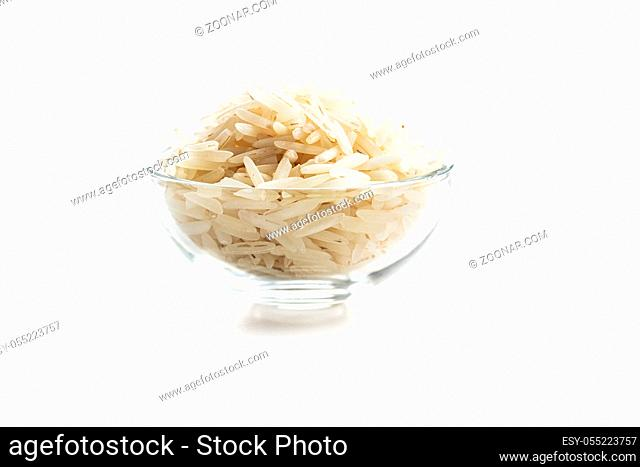 Uncooked indian long rice in bowl isolated on white background