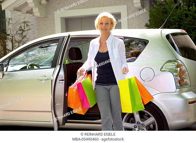 Woman with carrier bags at the car