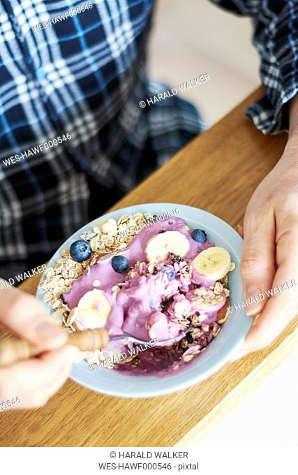 Man in pajamas eating granola with soy yogurt, blueberries and banana