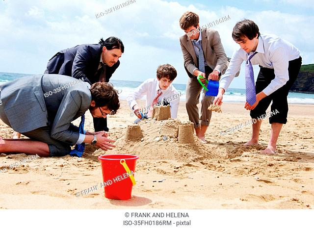 Businessmen building sand castle
