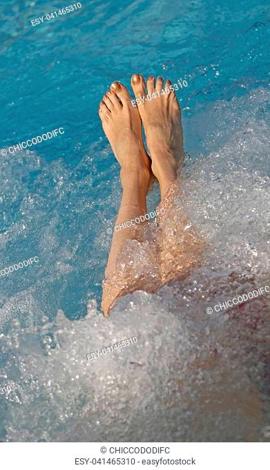 barefoot feet of the young woman during the hydromassage session to reactivate the blood circulation in the spa