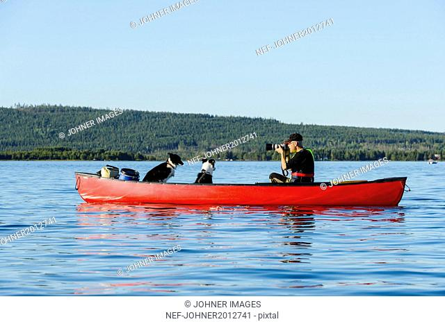 Man on rowboat taking picture