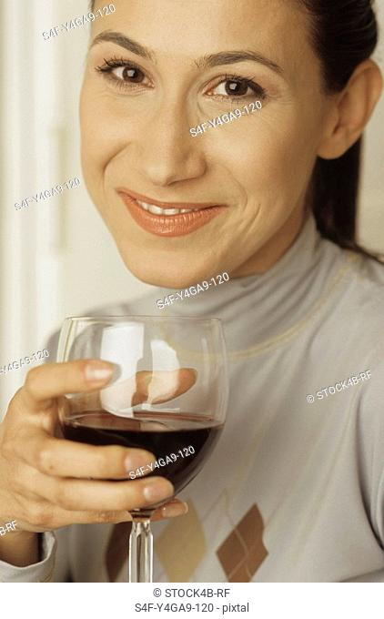Brownhaired Woman holding a Glass of Wine in her Hand - Alcohol - Enjoyment