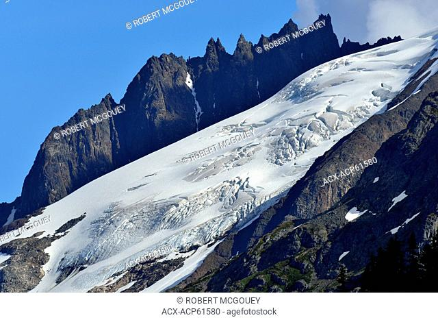Jagged mountain peaks surround this large snow covered glacier along highway 37A known as the Glacier Highway in northern British Columbia Canada