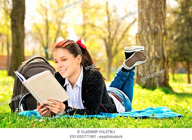 Student lying on a meadow reading a book. Girl reading a book in the park
