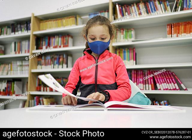Little girl wearing a medical mask and reading a book in a libra