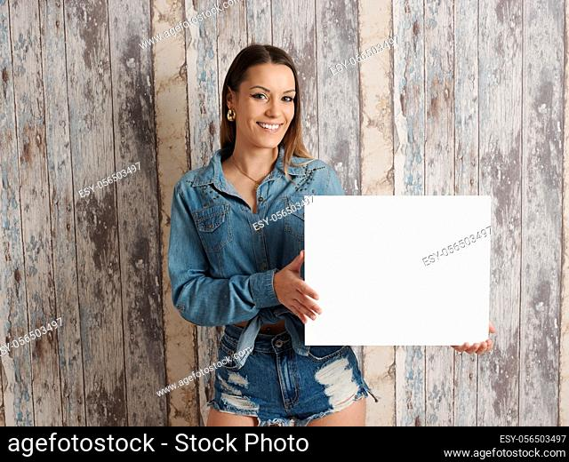 young pretty woman wearing cowboy costume and showing a poster