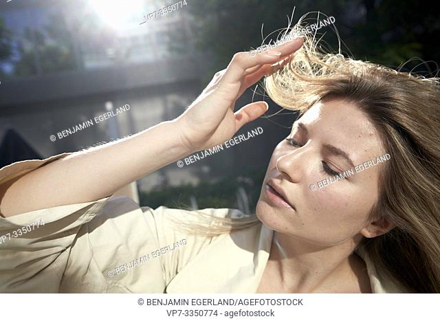 young sensitive woman playing with hairs
